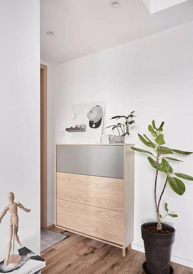 玄关距离短且狭窄,选择了一款体积小颜色轻的成品鞋柜,搭配一张灰色地毯,形成室外进入室内的完美过渡。