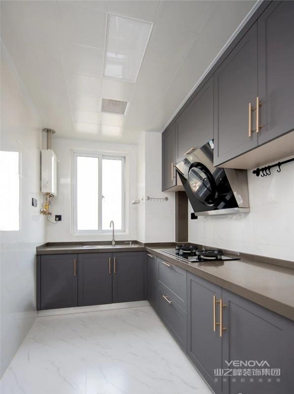 厨房,L型操作台面节约空间,灰色定制橱柜与深色操作面板在实用性上更为突出。浅色调墙地面调节厨房亮度,金属把手也让轻奢感蔓延到厨房空间。