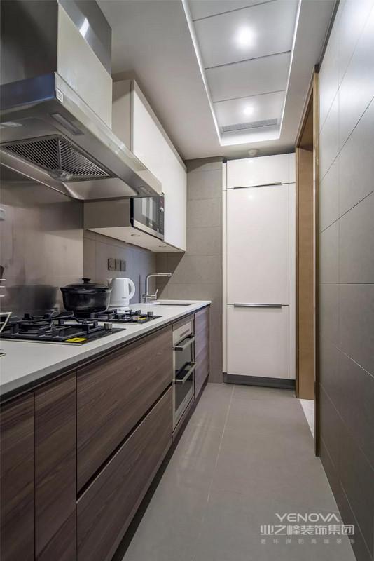 厨房的面积不大,还是一个狭长的空间,所以橱柜也是一字型的布局方案,设计师把冰箱嵌入到墙内,看起来更为整洁大方。