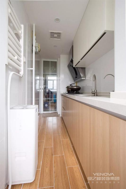 厨房是个狭长的空间,橱柜也做了一字形的布局,白色的吊柜搭配木色的地柜,整个厨房空间给人一种简洁又舒适的感觉。