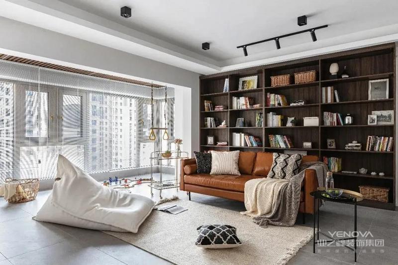 客厅没有设置电视或者投影仪,而是采用了一整面的书柜墙代替。沙发则采用了较为轻巧的款式,将原客餐厅猪肝色的木地板换为了水泥瓷砖,美观大气。