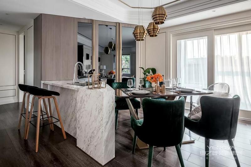 餐厅的餐桌靠着一个大理石吧台摆放,加装水槽方便日常使用。在餐厅侧方的墙面做了镜面墙的设计,整个餐厅的搭配有着复古的感觉