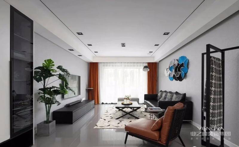 设计师以黑白灰为主色调,焦糖色单人沙发与橙色窗帘点亮空间。黑色皮质沙发质感满满,与黑色茶几一起稳住空间气场。背景墙上黑白灰与蓝配色的墙饰别具一格,时尚而又独特。