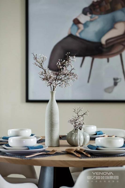 餐厅处选择了款式简洁的木质圆餐桌,在餐桌上摆放一些精致的摆设,让餐厅看起来更有格调