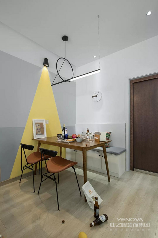 餐厅这个区域设计成了卡座式的,让它拥有更多的储物空间。亮黄色的三角形刷在墙面上,让餐厅看起来更有活力感。