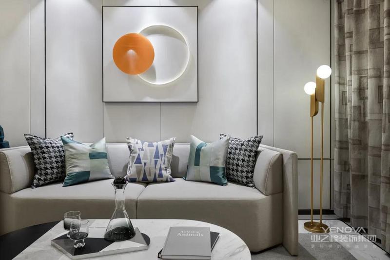 沙发墙以硬包背景墙基础,挂上一副方形的装饰画,画面内容是一个圆环+黄色的圈圈,布置灰色沙发,侧边的金属落地灯,呈现出一种华丽活泼的高级画面感