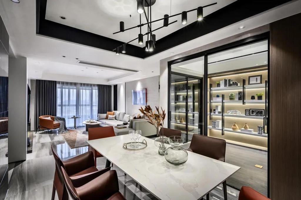 白色的石材台面基础,布置棕色的餐椅,餐桌上摆着玻璃器皿,结合顶上黑色的吊灯,让用餐氛围优雅华丽而端庄。