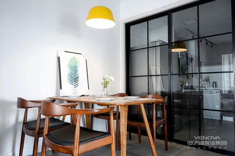 原木风的餐桌椅搭配黑色的坐垫,餐桌上摆放了干花和绿植装饰画作为点缀,黄色的吊灯让餐厅更显活力