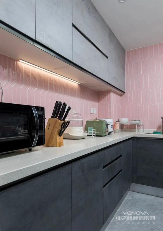灰色地砖搭配灰色橱柜门 粉色的墙砖让料理 空间充满少女感 吊柜下方补充照明