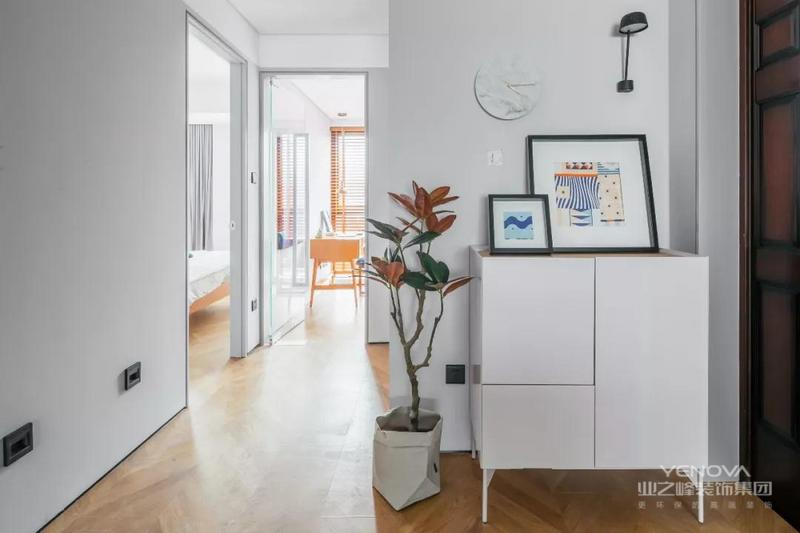 玄关摆放了一张白色小鞋柜,布置上绿植与装饰画,以及大理石挂钟、黑色壁灯,简约而舒适。