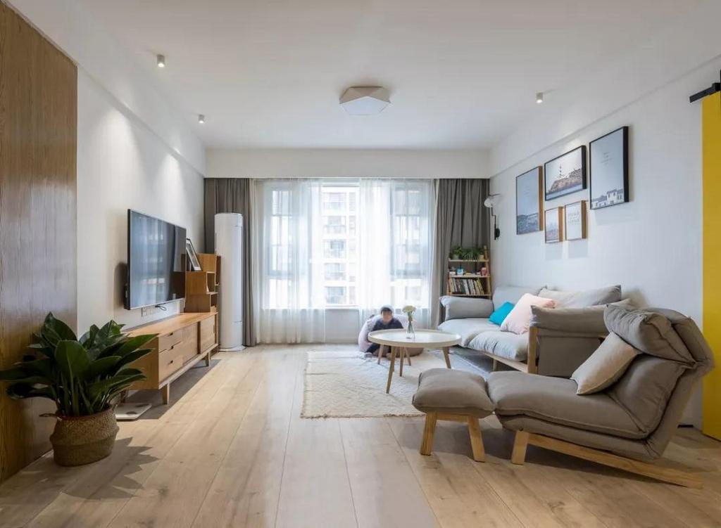 客厅通铺大尺寸木质地板,提升空间气质。背景墙上的组合挂画,给客厅增添了一些文艺氛围。