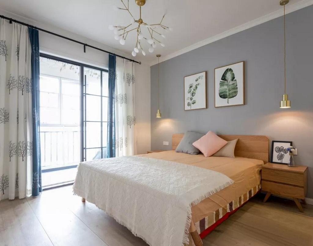 蓝白相搭的绣花树窗帘,与墙上挂画相互呼应,显得清新干净。铺上了暖色调床品的木质床,柔软舒适中带着自然恬淡的气息。