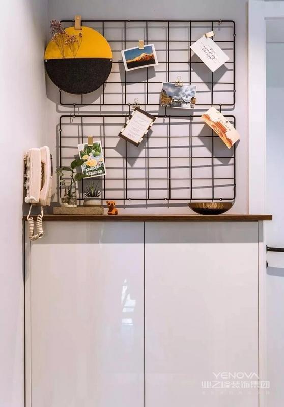 入户的小玄关,在入户门的对面摆放一个小矮柜,上方做铁丝网结合绿植、照片等的装饰设计,打造一个简洁的端景台。