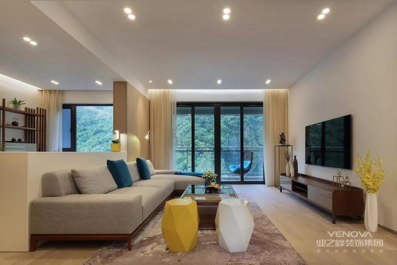 客厅和茶室之间以沙发和半墙作为隔断,整体以白色为主,用筒灯来代替主灯,显得非常简洁。原木风的沙发、茶几和电视柜,给家里增添温馨感