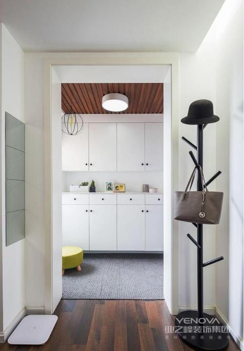 入户靠墙的一侧定制了一个鞋柜,上下两层。上面储物下面放鞋,中间的台面可以放一些钥匙等小物品。因为是一个三口之家,不用担心储物空间不够。吊顶采用的是生态木吊顶,提升整体质感
