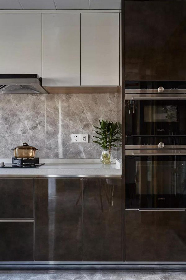 厨房空间选用纯白上柜搭配深棕纹理下柜,在视觉层次上形成鲜明的对比;而亮面材质的精彩运用,也让整个厨房的格调大大提升。