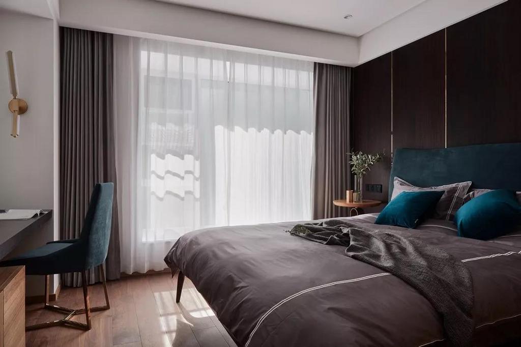 深色木质墙面与同色系窗帘、床品的巧妙搭配,给卧室注入了一股宁静、沉稳却不失高雅的格调。