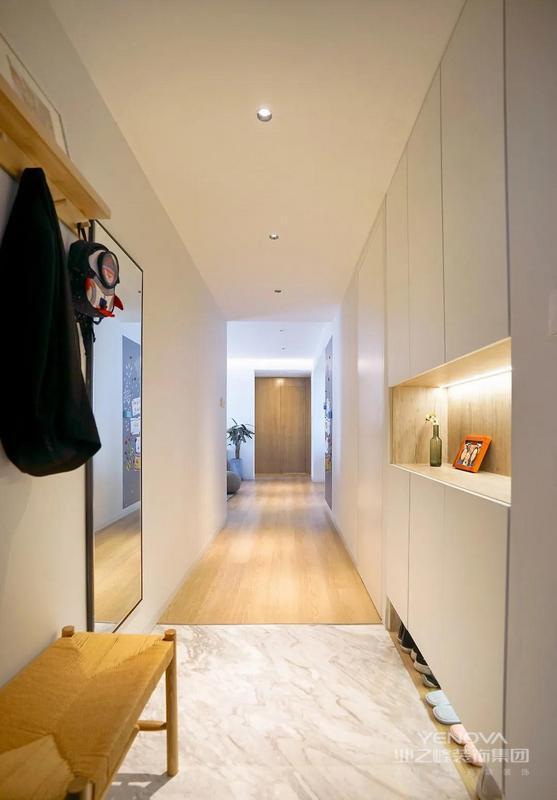 入户玄关,鞋柜是利用客卧墙拆除后做出来的,同时玄关地面用石材和室内地板区分,增加功能的同时视觉上弱化走廊长度。