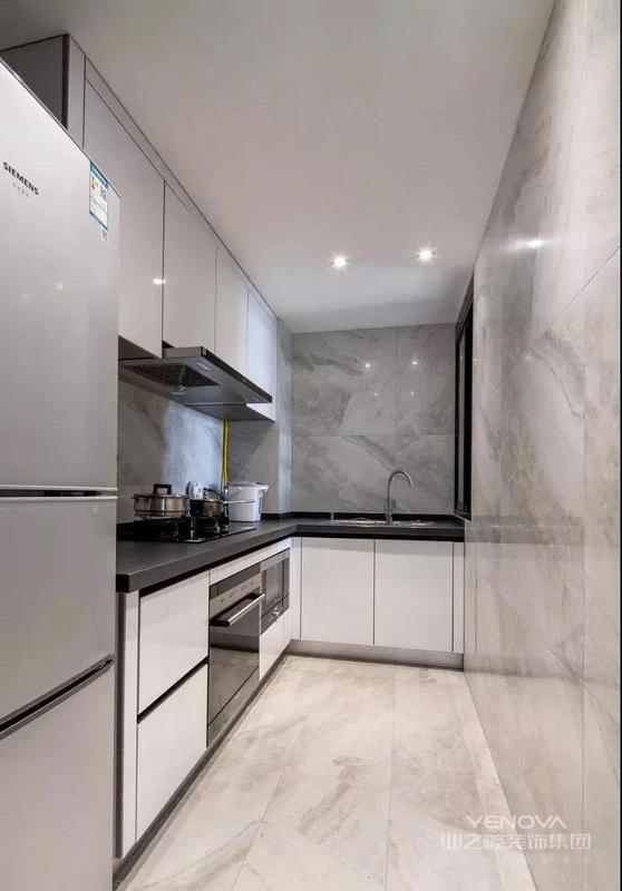 厨房空间,L型的橱柜布局,冰箱被摆放在柜子的边上。厨房的墙地面通铺大理石瓷砖,搭配白加黑的橱柜、台面,非常大气。
