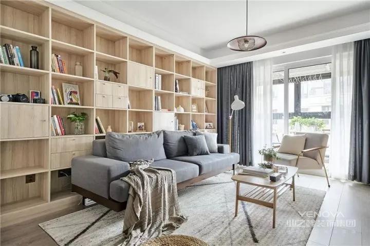 原木色的收纳柜体定制成书架充当沙发墙,搭配灰色布艺沙发,丝绒质感地毯和简约轻巧的椭圆茶几,自然舒适的惬意感油然而生