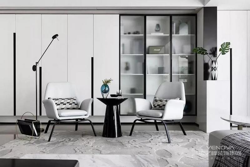 客厅还布置休闲桌椅,后方收纳柜加入玻璃柜门的设计,让空间显得更加简洁时尚