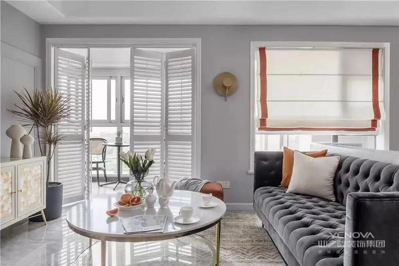 客厅与阳台相接,两扇折叠式百叶门既方便通风,又节省空间。沙发背景墙砌成半墙的造型,发挥隔而不断的作用