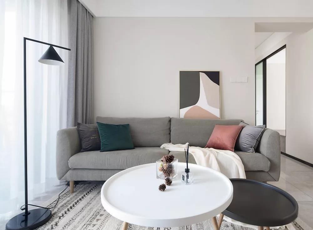 灰色沙发柔软的恰到好处,脚踩在地毯上享受片刻的放松,挂画也是随性而放。