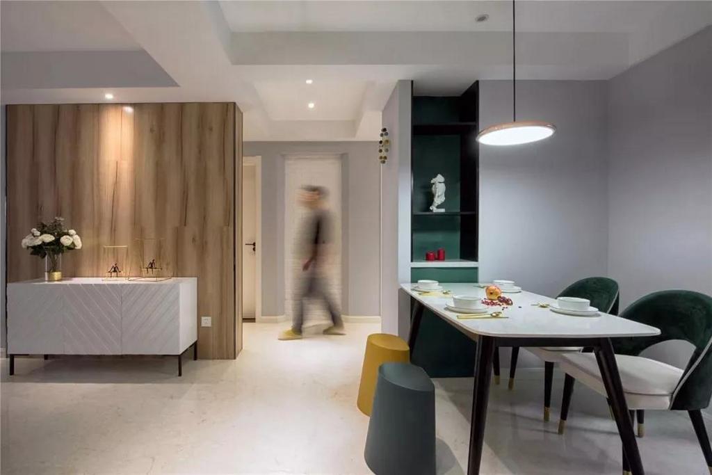 另一侧是被刷成了灰色和做了木饰面板的设计,玄关走廊的地面铺设灰色的地砖,和餐厅处的木纹砖相间,让空间得以划分。
