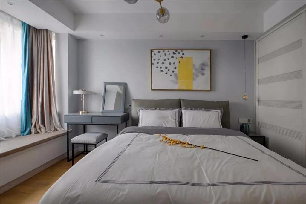 主卧室的软装延续了整体的灰色调,很喜欢这款灰色的布艺床,舒适的靠背让屋主可以躺在床上看书。