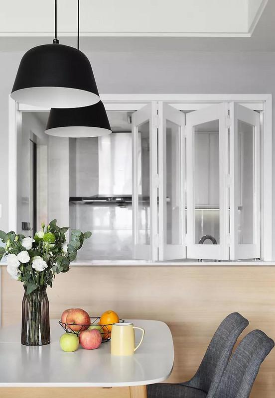 餐厅与厨房之间设计了一个小吧台,把白框玻璃折叠窗打开,就形成了一个交流互动的路线。