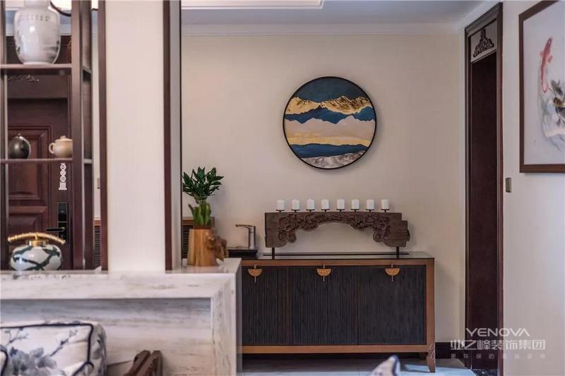 入户的玄关门厅一侧摆放了一个端景台,端景台上方有着禅意的装饰品和圆形挂画,在不经意间流露出独特的雅致感。