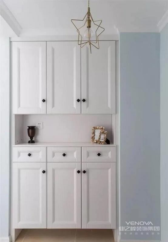 玄关柜设计成白色的简约柜门,美观大方还特别实用。中间台面可以放一些钥匙类的小物件,底部悬空摆放拖鞋,设计合理。星状金属吊灯增加了一丝俏皮