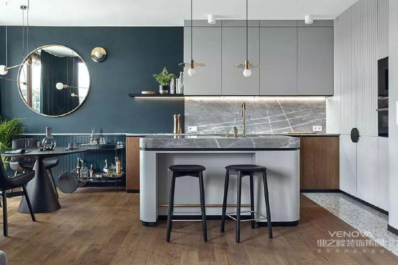 开放式的厨房以浅灰色为界线划分底部原木色的厨柜门与木地板相呼应大理石台面、金色水龙头看起来质感十足