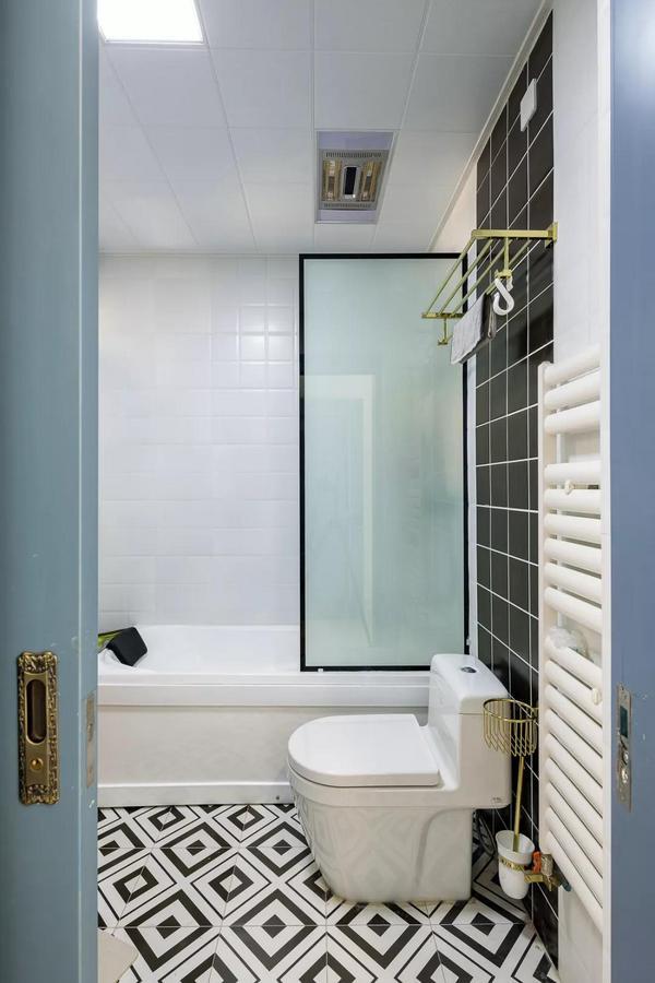 卫生间装了个浴缸,用玻璃作隔断作为干湿分区,黑白回字形的地砖,结合白色与黑色的墙面,打造出简约时尚的格调。
