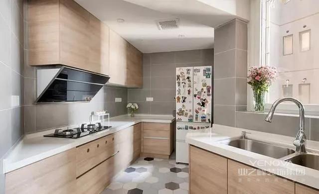 厨房形状怪异,但利用率高。同样以木色无把手按压式的橱柜为主,搭配大块灰色的墙砖,整体显得干净利落。冰箱上贴满各种冰箱贴,俏皮可爱。双水槽的设计满足了多人共用厨房的需求。