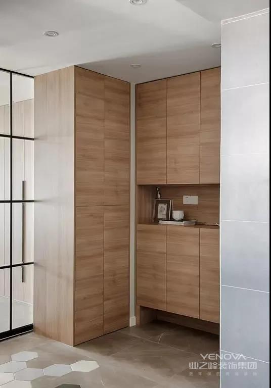 入户玄关设有一面木色的柜子,无把手的按压式设计,自然大方,既美观又有实用性。留有中空位置和底空位置,方便收纳小物件和码放鞋子。