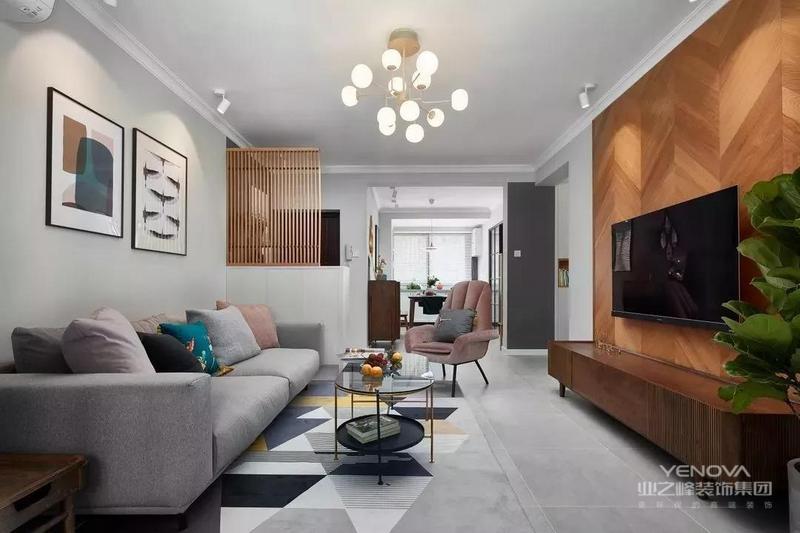 客厅的电视背景墙用鱼骨拼的木地板组成,浅灰色的布艺沙发搭配灰色系的哑光砖,还有一款几何形的拼色地毯,整个客厅给人一种轻松、舒服的感觉。