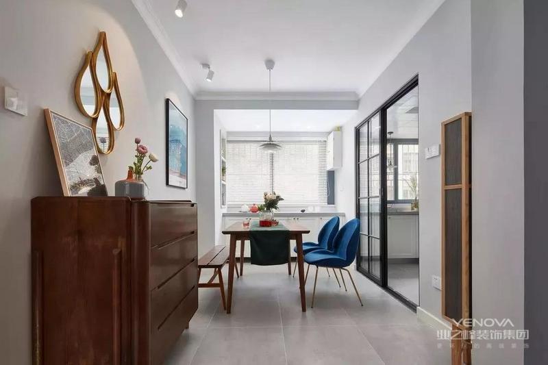 餐厅位于房子的另一侧,和客厅做了相同的灰色哑光砖,除了斗柜之外,靠窗的位置还设计了地柜和墙面收纳格的组合式收纳设计。