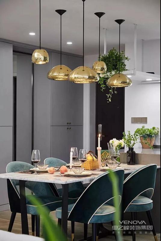 入户的玄关走廊和开放式的餐厨连在一起,在餐厨的另一侧做了到顶的柜子,大理石台面和金属吊灯的设计,让餐厅显得格外精致、优雅。
