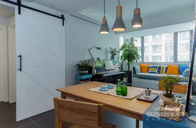 餐厅和卧室走廊之间加装了一扇谷仓门,原木风的餐桌椅搭配简洁吊灯,显得轻松自在。餐厅的边上还有一个休闲区,做了一个卡座。