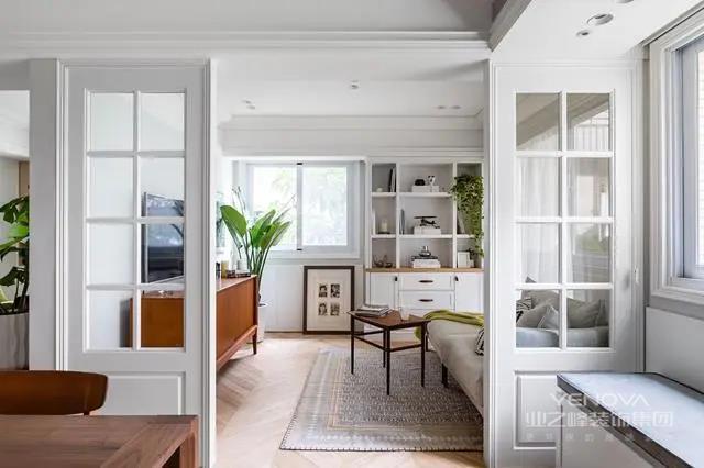 从餐厅望向客厅,中间用一扇白色玻璃门隔断,形成分区的效果