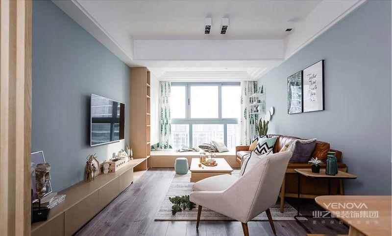 将阳台和客厅打通,一体化设计,空间显得很宽敞,蓝色的墙面搭配复合木地板,看起来很有北欧风的感觉。