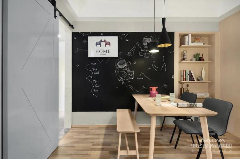 餐厅背景墙做了一面黑板墙+收纳书架,结合黑色的吊灯与餐椅,木色与黑色的结合,在原木色的餐桌与板凳布置下,营造出一种文艺舒适的自然气息。