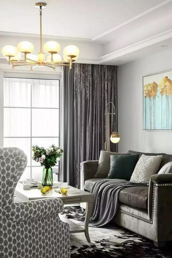丝绒美式三人沙发与窗帘的材质,有响应的效果,低调内敛,却又流露出一种高贵优雅的气质。金色吊灯与落地灯有锦上添花的效果。