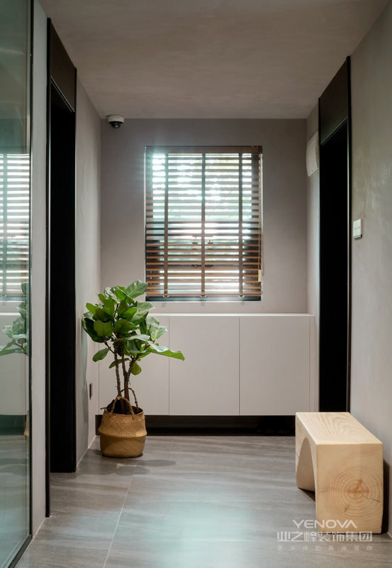 玄关选用简约的灰色为主调,搭配木色的百叶帘、坐凳,以及清新怡人的琴叶榕,带给屋主最自然纯粹的视觉品味