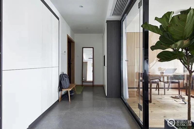 玄关在灰色的地砖空间,两侧定制收纳柜,布置全身镜与换鞋凳,让进门后的玄关空间显得更加简约优雅,而透着玻璃后的书房空间,也是增加了玄关的通透感与采光。