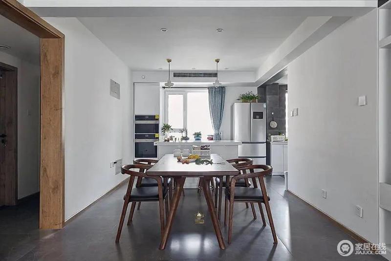 餐厅布置胡桃木餐桌椅布置,旁边还有一个西厨中岛台,在靠窗定制餐边柜+电器柜与冰箱摆放,简洁的空间下,布置出一个简雅华丽的用餐体验。
