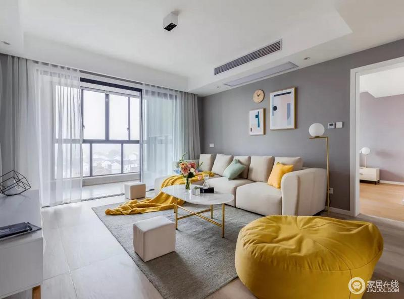 整个客厅因玻璃推拉门瞬间充满了阳光,光线让整个客厅也明亮清新;灰色的墙面与米色系沙发形成一种柔和的对比,而黄色软包沙发、靠垫渲染着和暖。