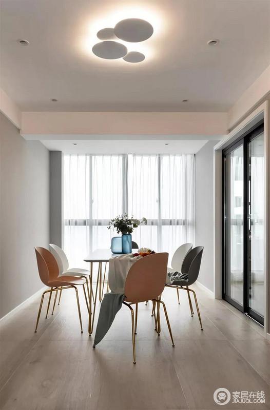 因为靠近窗户的原因,整个餐桌区域光线通透明亮,配套的白色的餐桌+颜色不同的餐椅,以及桌上摆放的装饰花都彰显出主人的品位。