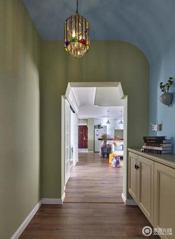 走廊侧边摆上一个柜子,柜面可以摆放一些书籍或绿植,而天花的这个彩色金属框架的吊灯,结合蓝色弧形的吊顶,整个空间都显得清新浪漫大方。